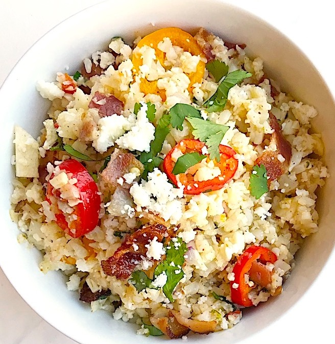 meican cauliflower rice in a bowl with cilantro, red bell pepper, cotija cheese and bacon