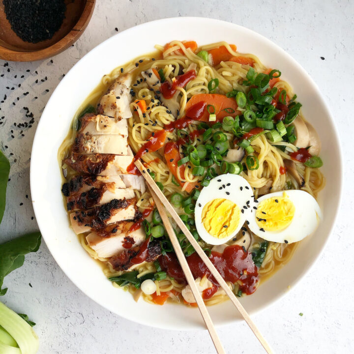 Ramen in a bowl topped with egg and chicken