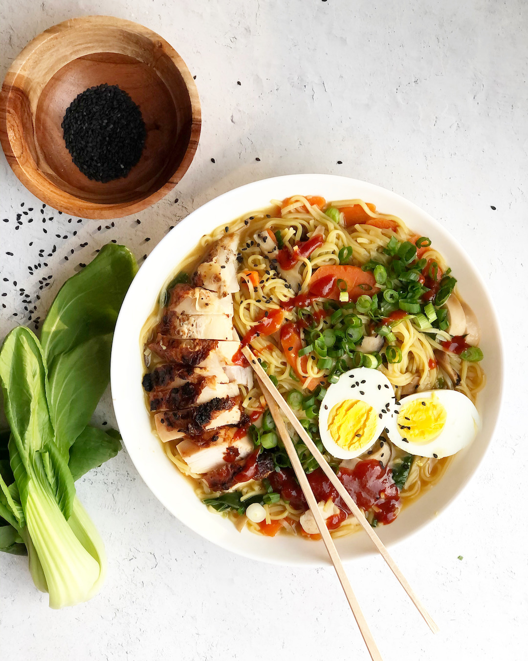 ramen in a bowl with chop sticks and bock choy and sesame seeds