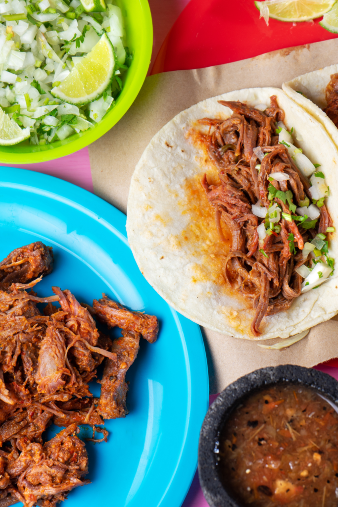 shreeded beef tacos with a plate of cilantro and onion and a plate of shredded beef