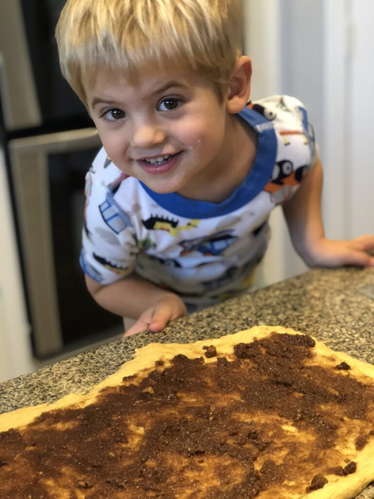 kids making cinnamon rolls