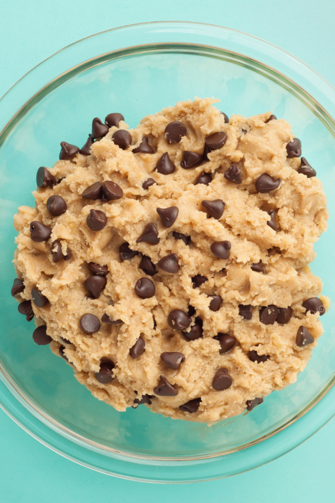 cookie dough in glass bowl with teal background