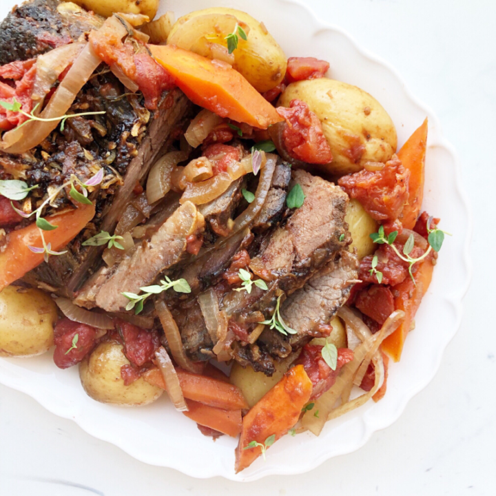 Crockpot roast with vegetables on a white platter