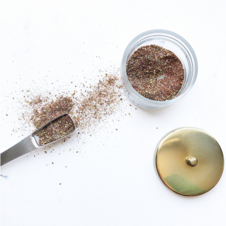 Taco seasoning in a glass jar on a white background