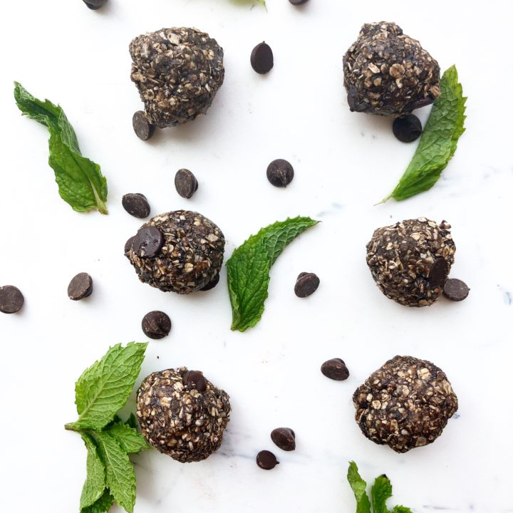 mint chocolate protein balls on a white background with fresh mint and chocolate chips scattered