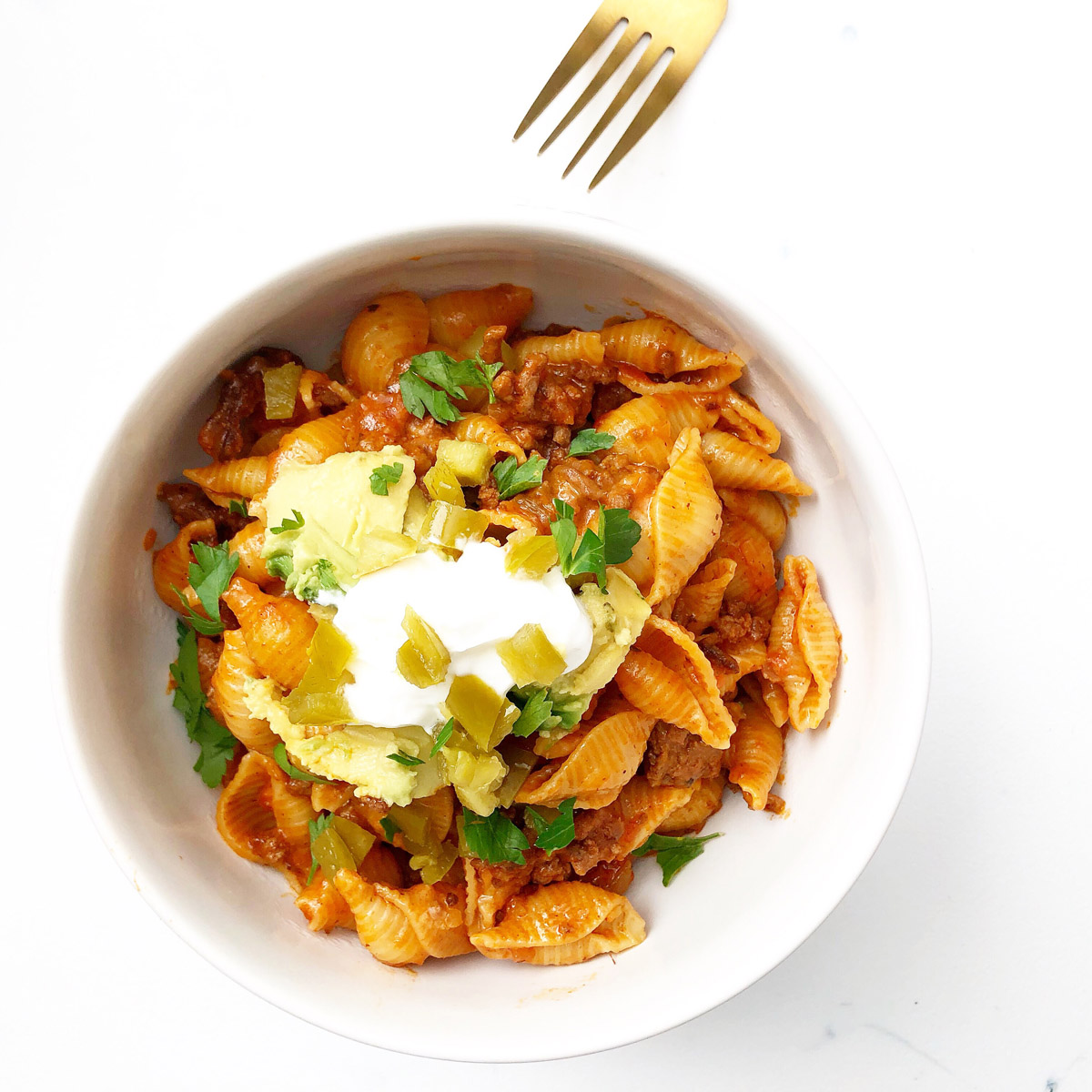 Pasta with ground beef, salsa and taco seasonings topped with greek yogurt jalapeno and cheese