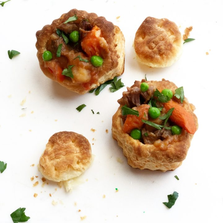 Beef stew in puff pastry cups on a white background