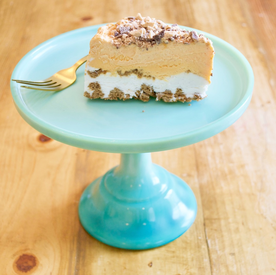 ice cream cake on a teal platter with a gold fork