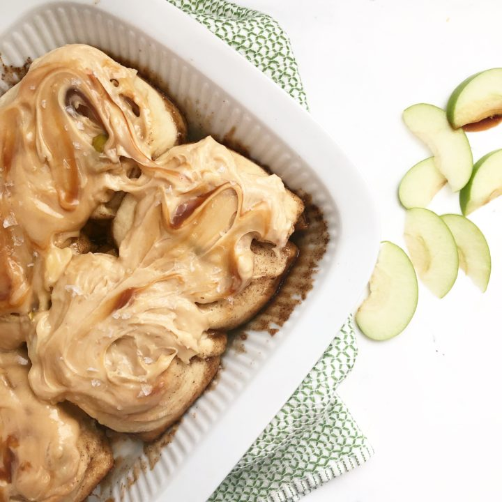 cinnamon rolls in a white baking dish with caramel frosting on a white background.