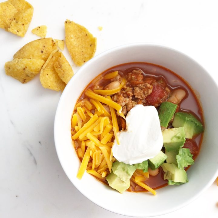 a white bowl filled with chili topped with cheddar cheese, sour cream, and avocado with corn chips on the side.