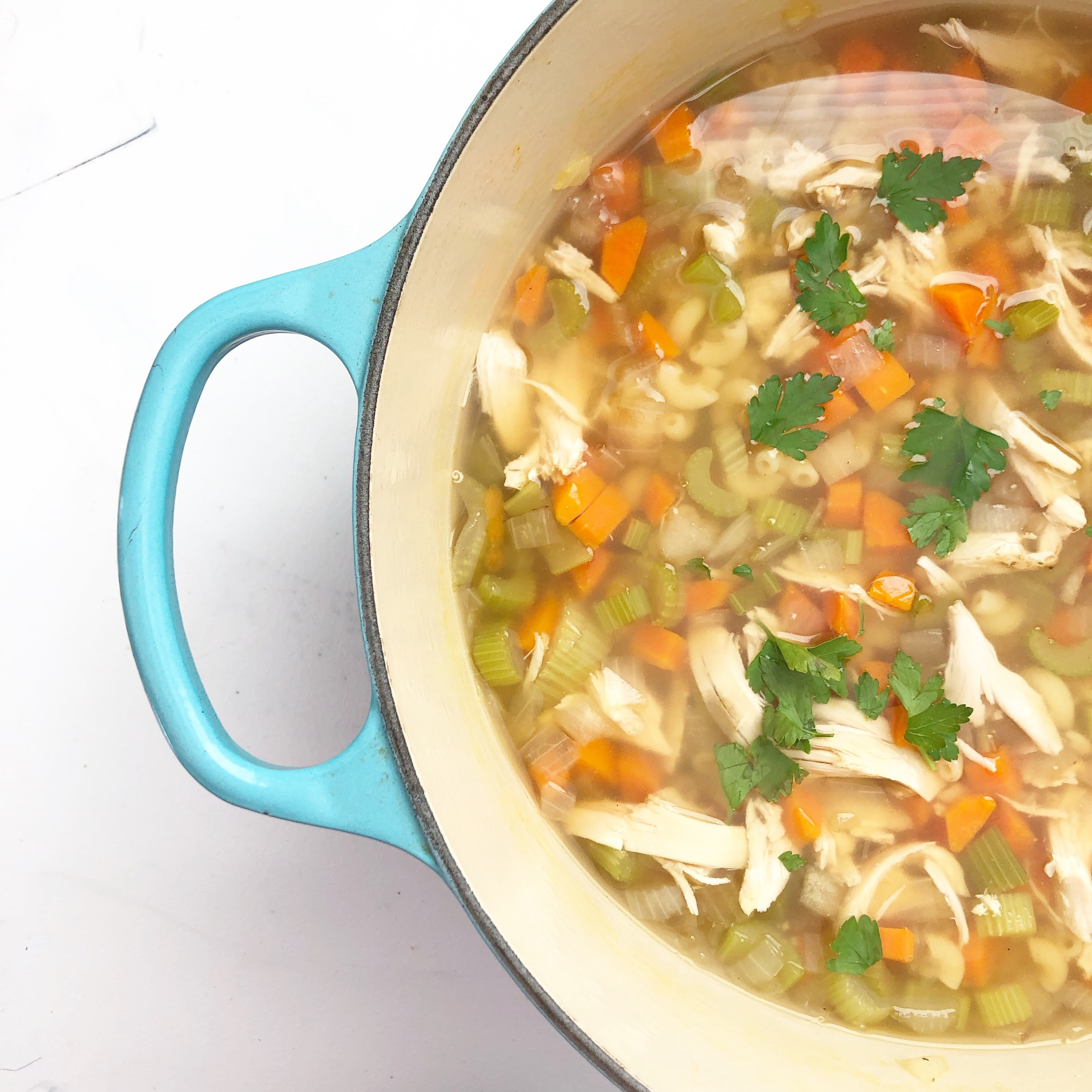 chicken noodle soup in teal dutch oven