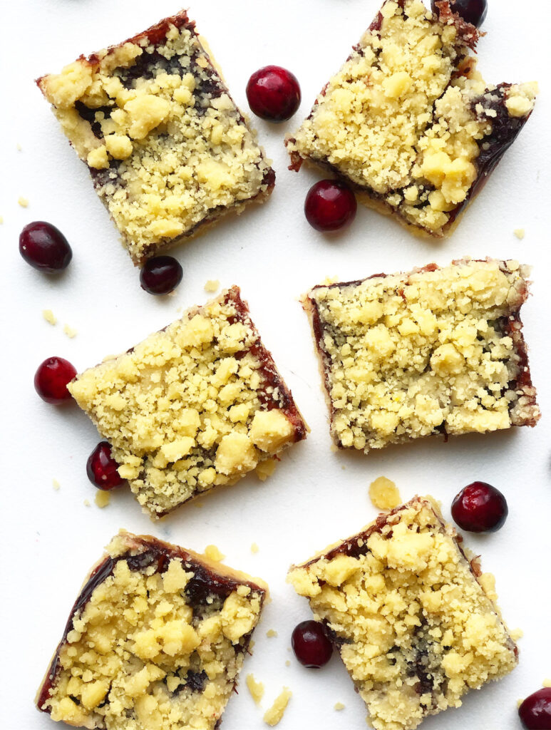 cranberry pie bars on a white background with fresh cranberries