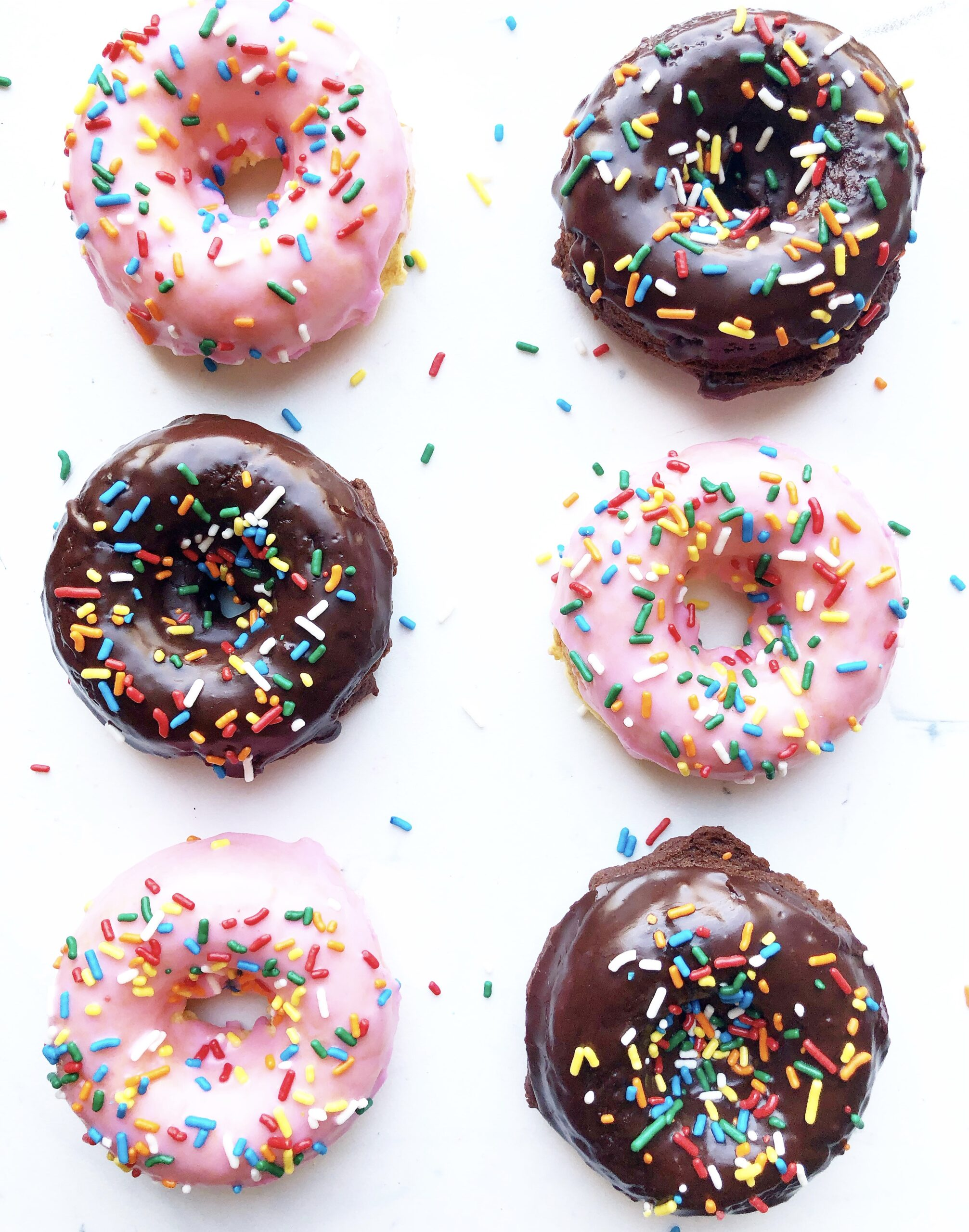pink iced and chocolate iced donuts with multicolored sprinkles.