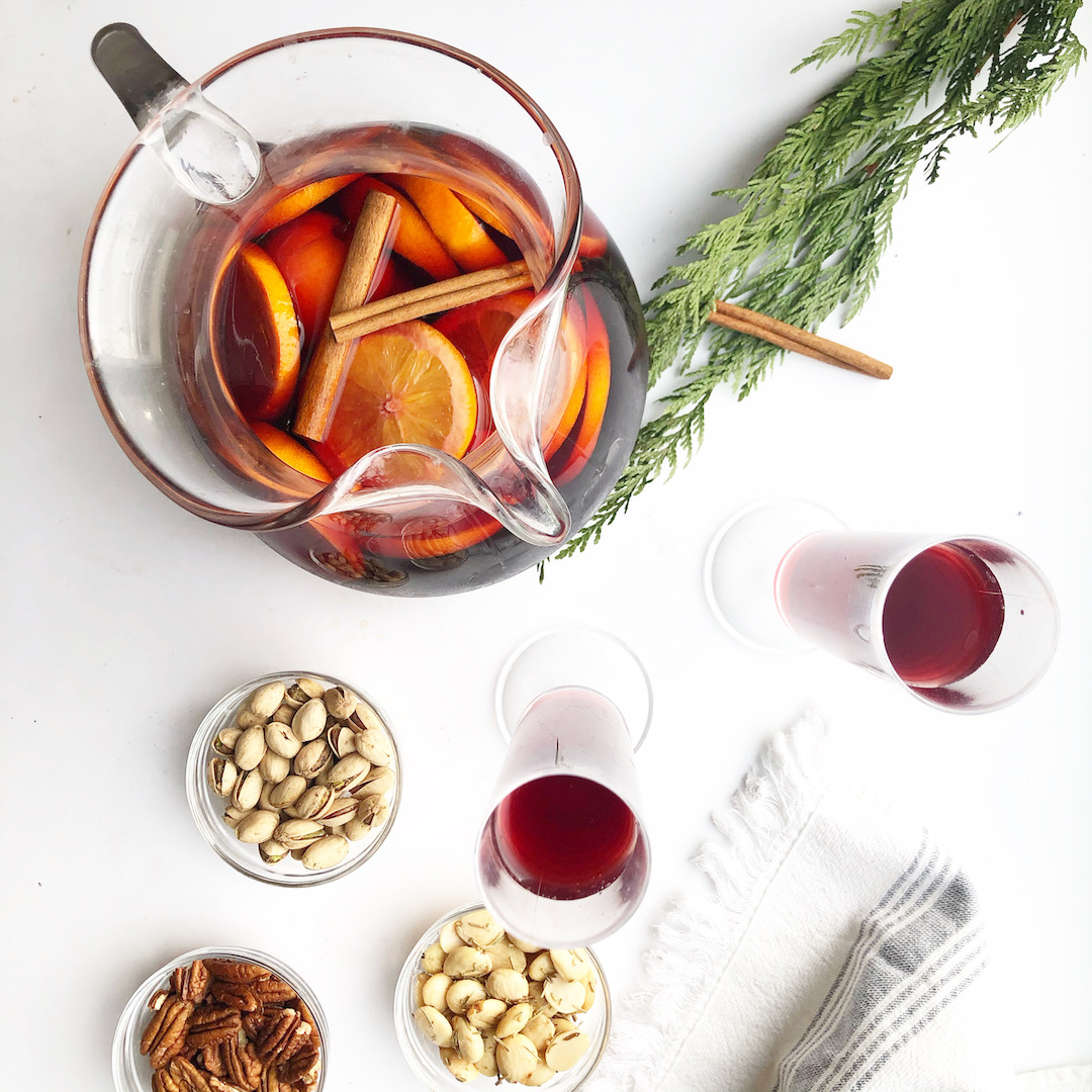 cranberry spritzer in pitcher with nuts in bowls