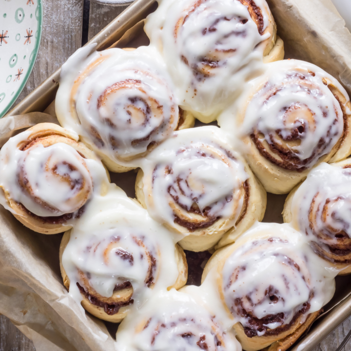 sourdough cinnamon rolls with icing in a pan