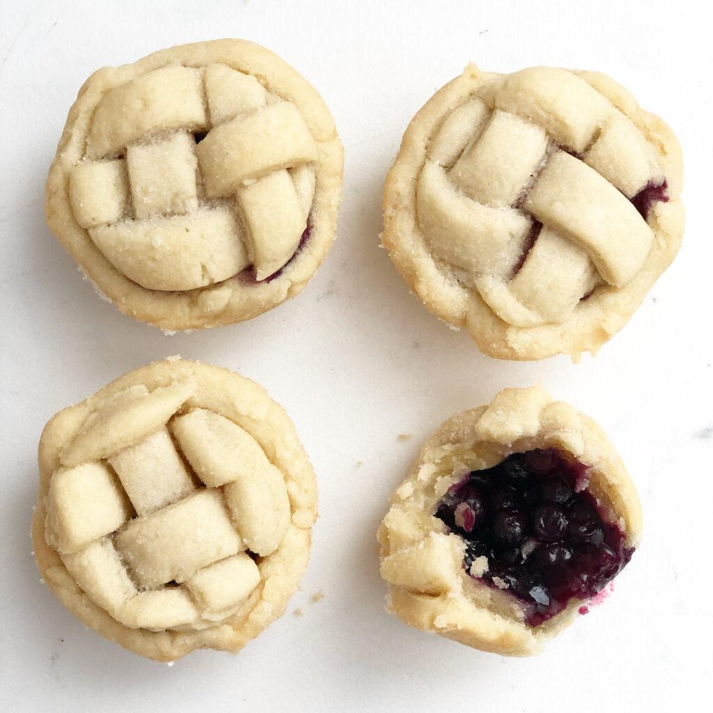 mini blueberry pies on white background