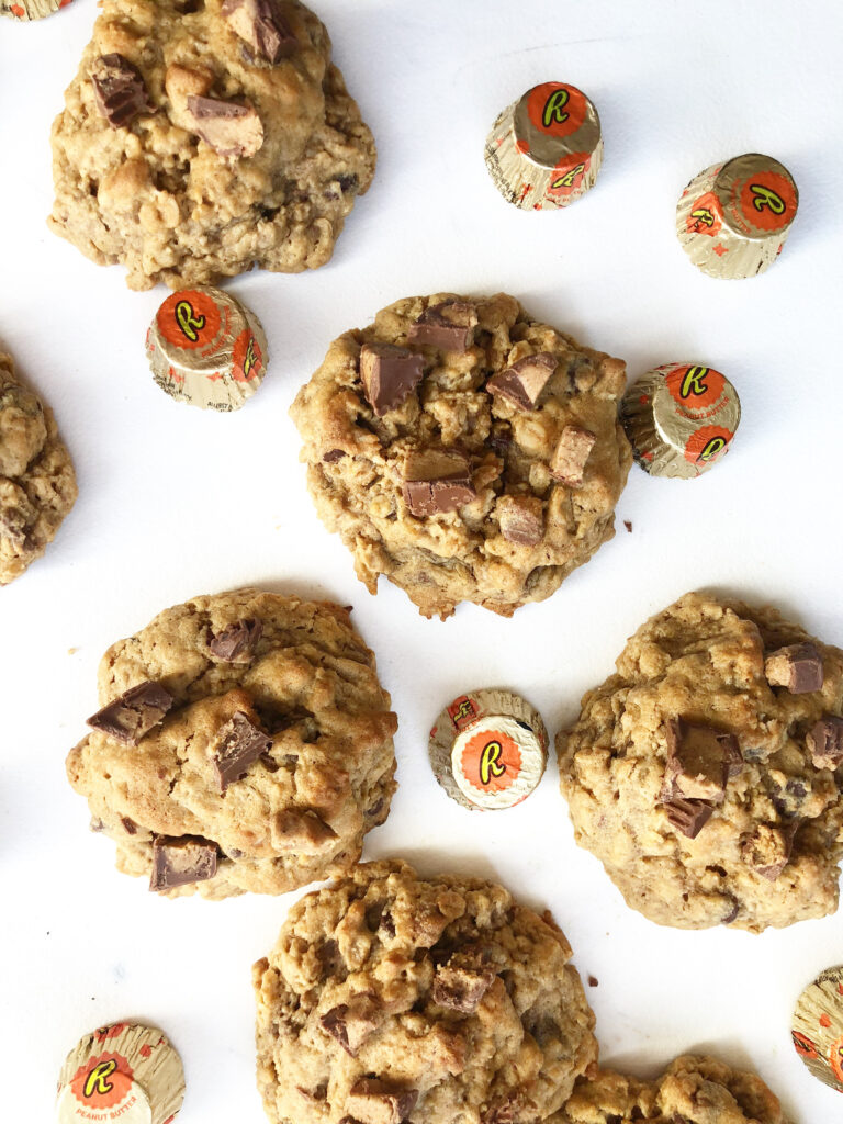peanut butter oatmeal cookies on a white plate with reese's candies around them