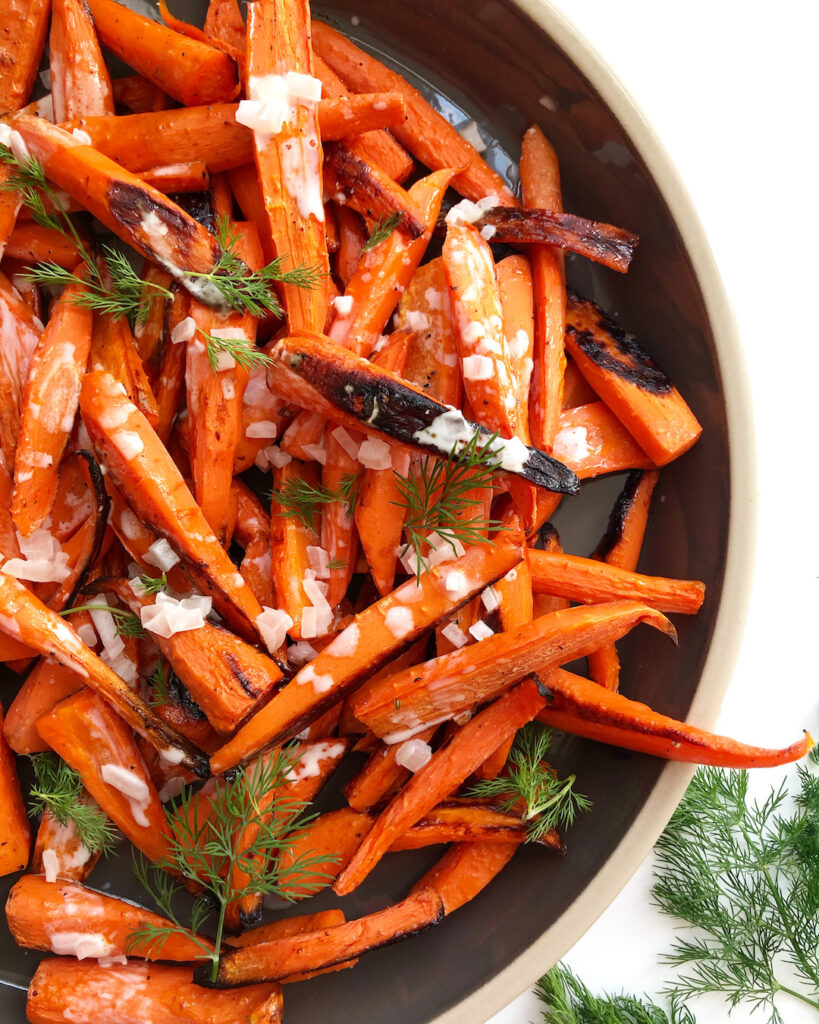 roasted carrots on a grey platter with fresh dill garnish