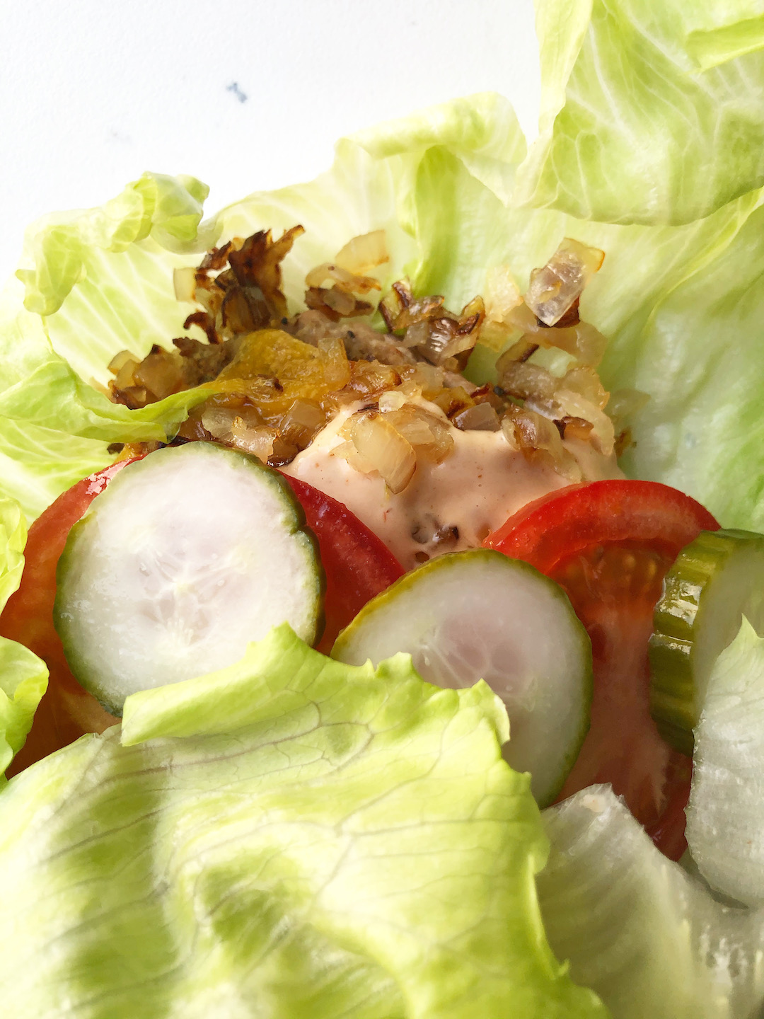 lettuce wrap burger with pickles, tomatoes, cheddar and grilled onions