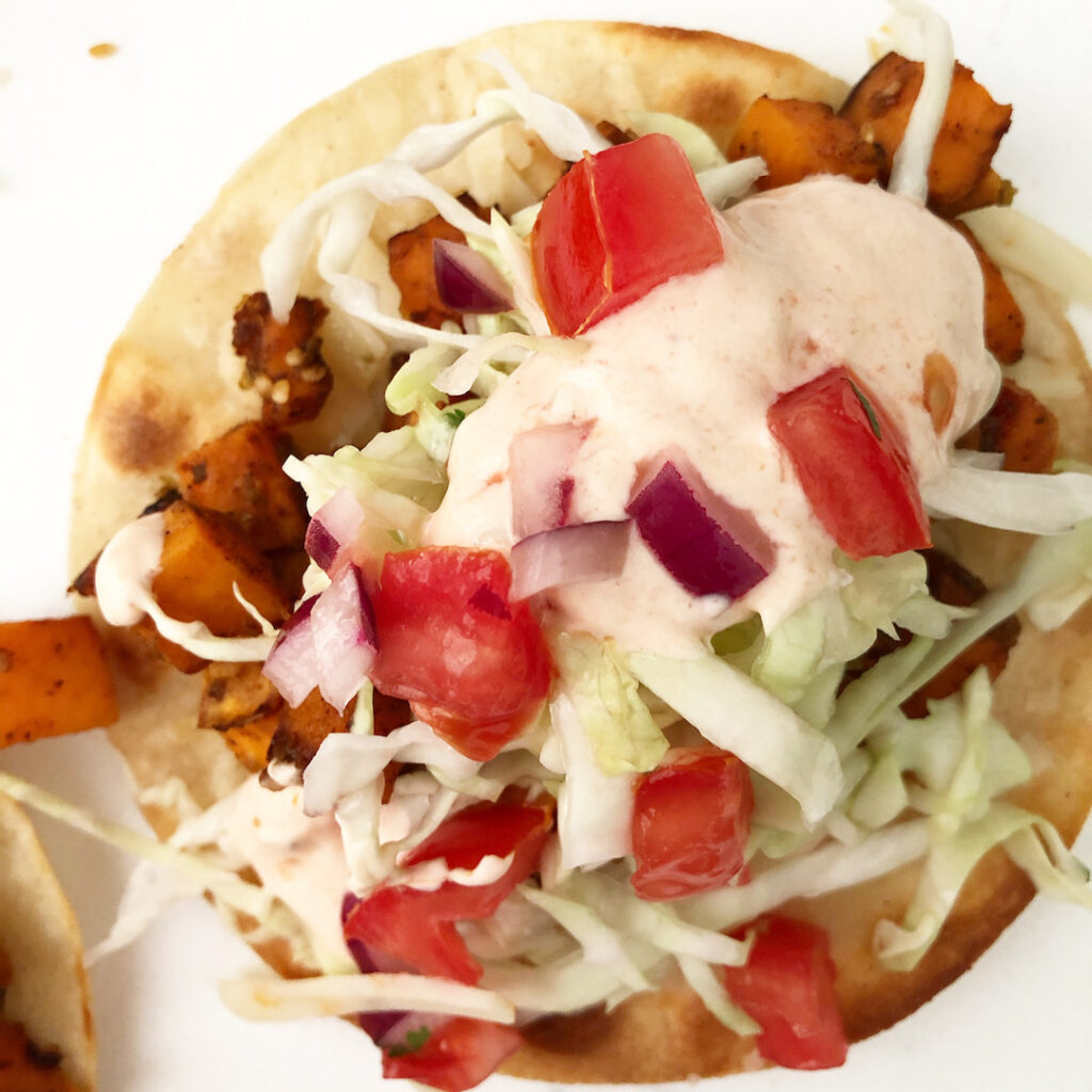 sweet potato taco topped with cabbage, crema and pico de gallo