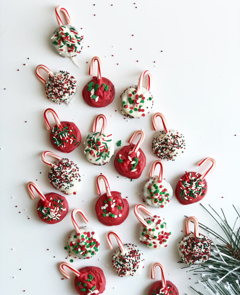 Oreo Christmas cookies that look like ornaments with candy canes and sprinkles