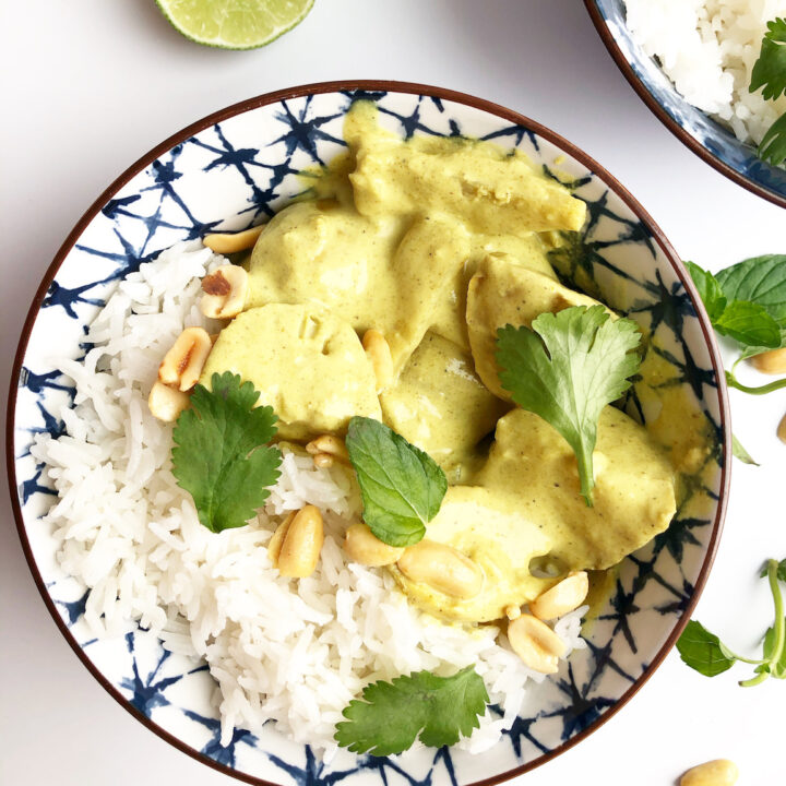 yellow curry with chicken and potatoes in a blue bowl with cilantro and peanuts on top