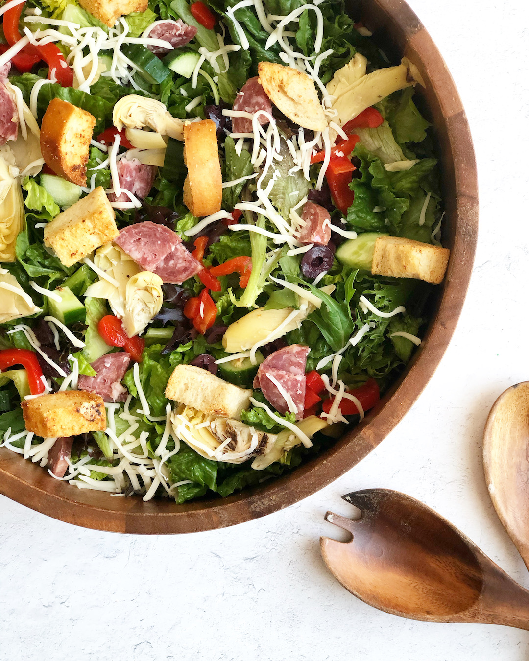Antipasto salad in wood bowl with wooden salad spoons