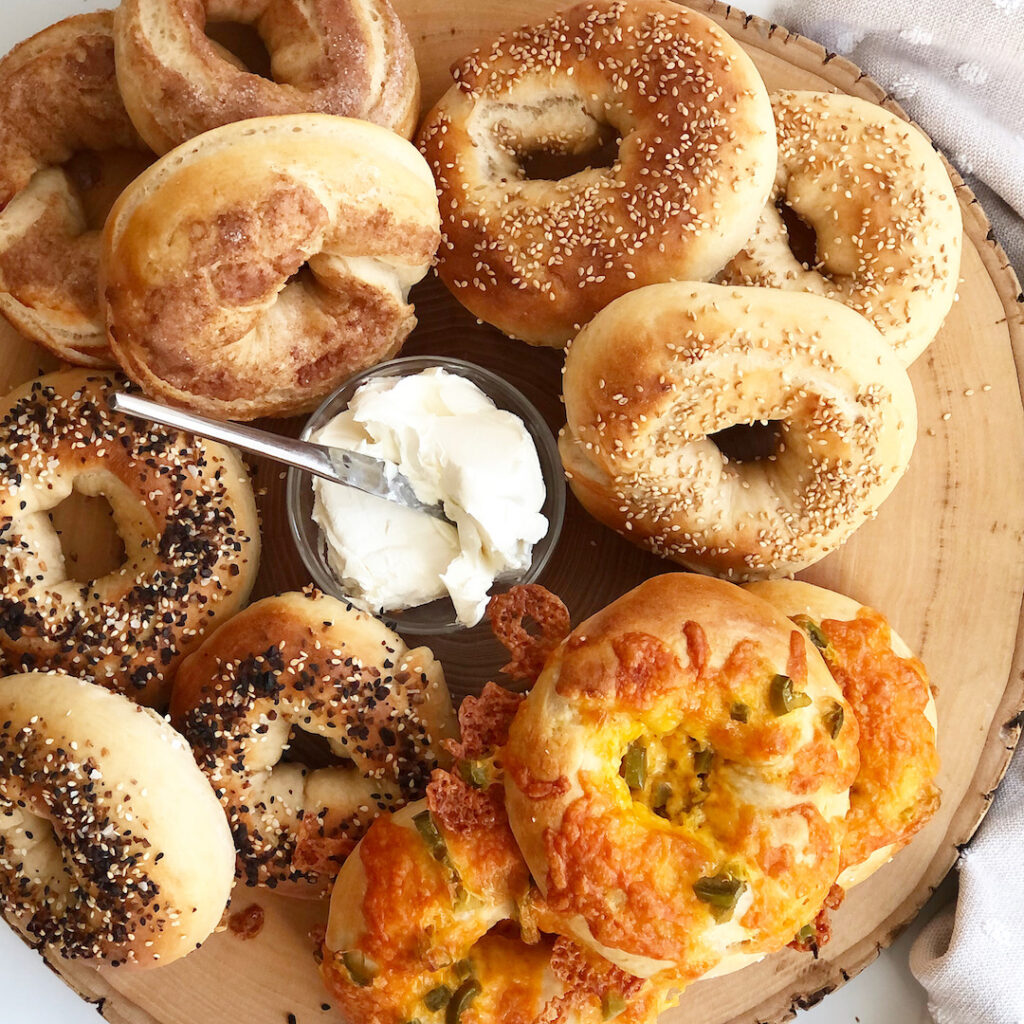 sourdough bagels on a wood board with cream cheese