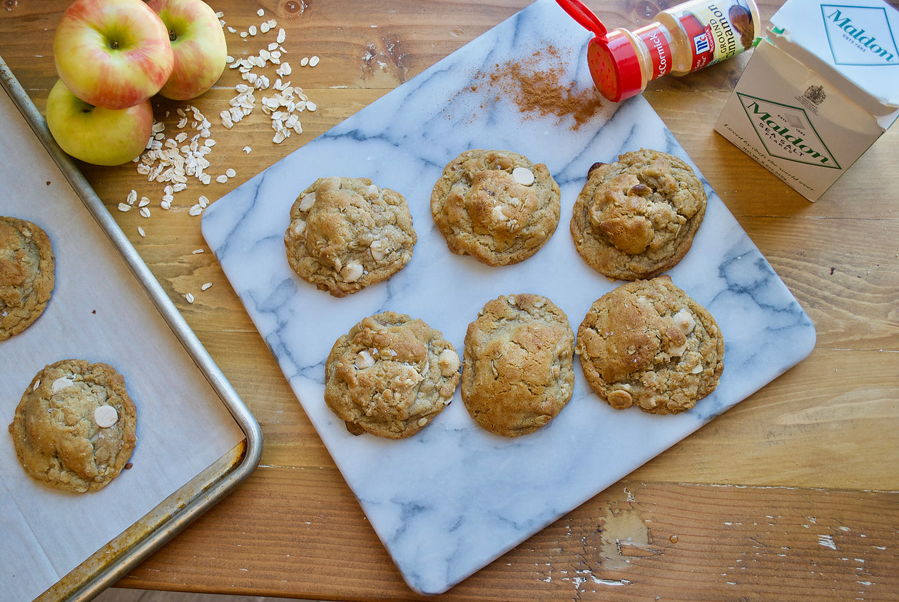 caramel apple cookies on a marble surface next to apples and cinnamon