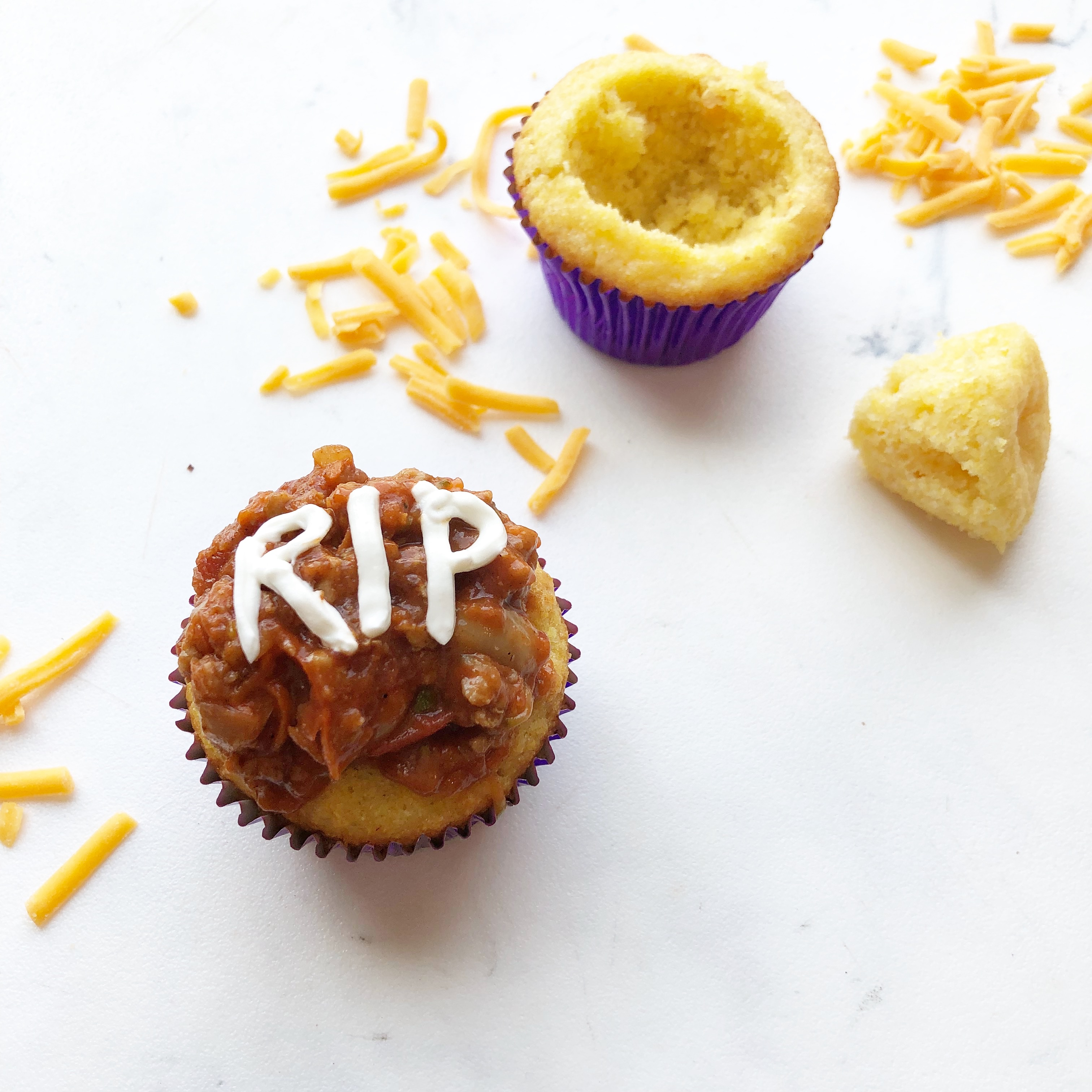 chili in corn bread muffin cups with the letters RIP written on then in sour cream